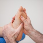 Podiatrist practicing reflexology on the foot of woman
